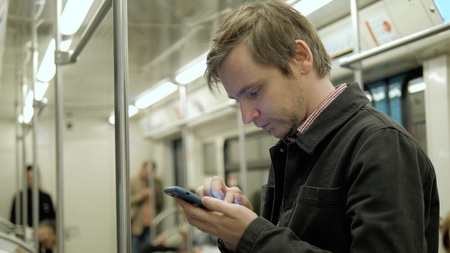 Businessman looking at his phone and waiting for subway in train