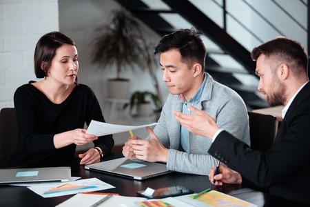Podejmowanie wspaniałych decyzji. Młoda piękna kobieta mężczyzna omawia coś z uśmiechem, podczas gdy jej współpracownicy słuchają jej siedzącej przy biurowym stole, grupa młodych freelancerów