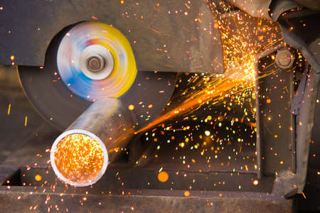 heated: Ð¡utting of a metal pipe with splashes of sparks