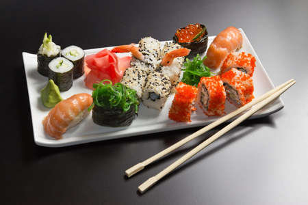 exotically: Japanese  seafood  sushi , roll and chopstick on a white plate