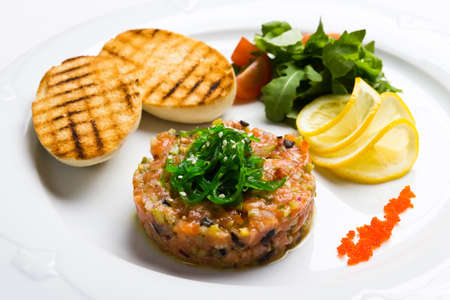 Fish tartare with caviar, vegetables and crackers Stock Photo
