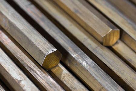 brass rod: background of a pile of brass hexagonal rods closeup