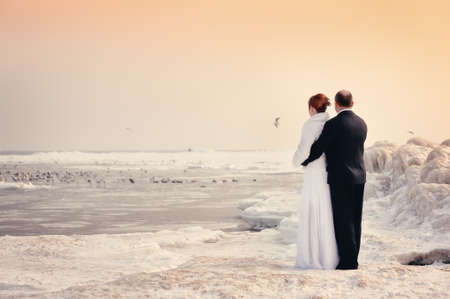 The groom and the bride look at the stood sea