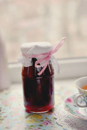 Bank of jam of crimson color with a cup of tea Stock Photo - 13321084
