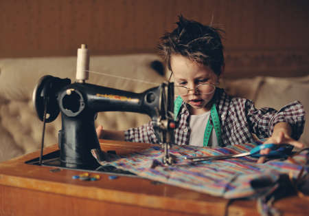 satisfies: The stylish boy wearing spectacles behind the sewing machine with scissors Stock Photo