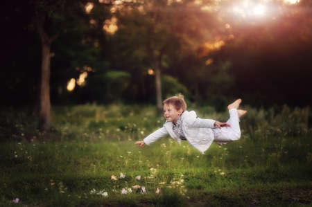 The boy in a white suit soars over a grass