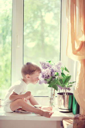 The child sits on a window sill at a window near to a lilac and smells aroma of flowers photo