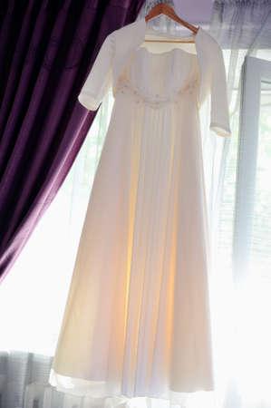 hangs: against a window the white wedding dress hangs