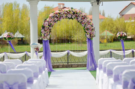 natural arch: wedding arbor with a flower arch and white chairs