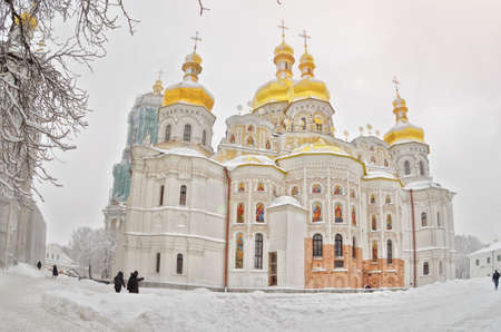 through snow-covered trees the church with gold domes photo