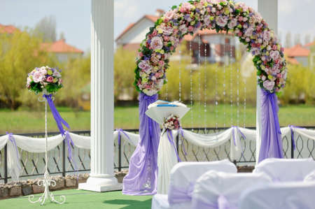wedding arbor with a flower arch and white chairs