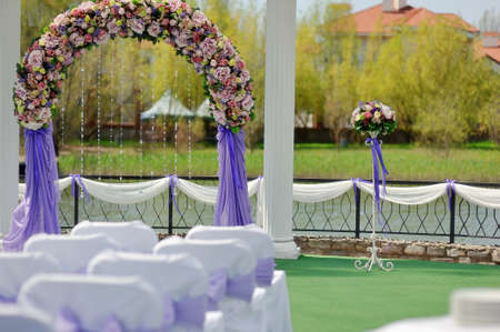 wedding arbor with a flower arch and white chairs photo