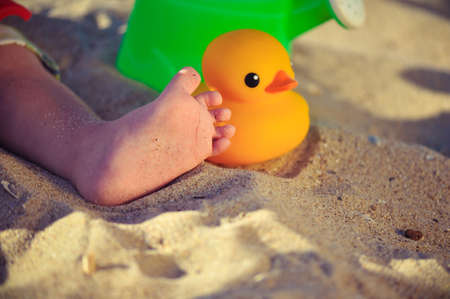 overindulgence: on sand in water a leg of the child and a toy