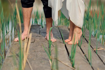 overindulgence: On the wooden bridge bare feet of the newly-married couple