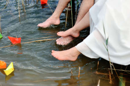 Bare feet of the newly-married couple hang down over water where paper ships float photo
