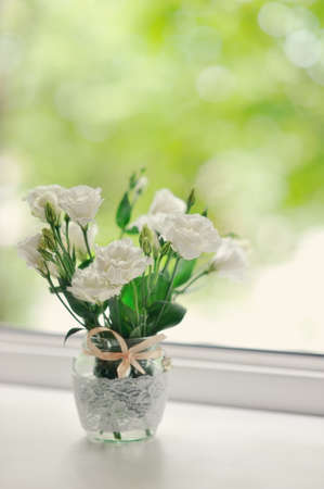 Bouquet of scarlet roses in a pot on a window sill early in photo