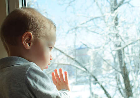 the kid looks out of the window on a winter landscape photo