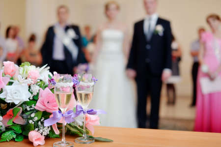 on a white table the wedding bouquet lies and nearby there are glasses photo