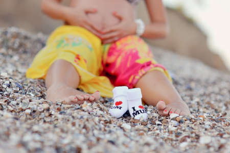 on sand the pregnant woman and a close up of her foot and children s socks sits photo