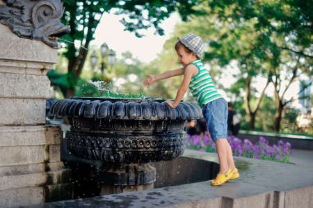 sun drenched: the boy at a fountain Stock Photo