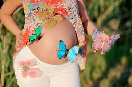 stomach of the pregnant woman and multi-colored butterflies photo