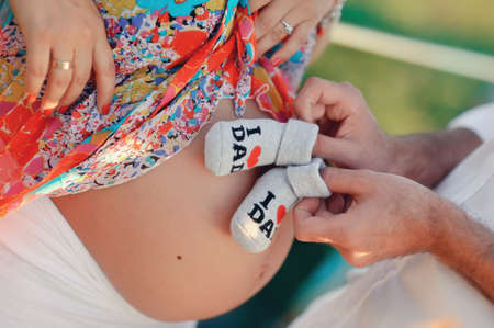 s stomach: stomach of the pregnant woman and small children s socks