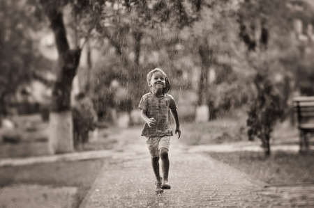 the boy jumps under a summer rain in park Stock Photo
