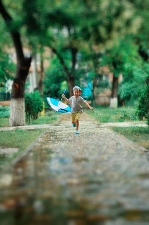 under a summer rain the boy walks and jumps on pools Stock Photo
