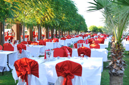 Long lines of festively decorated tables and with red bows chairs