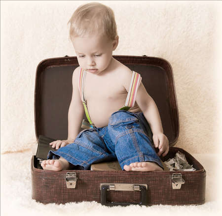 the child in jeans sits on an old suitcase