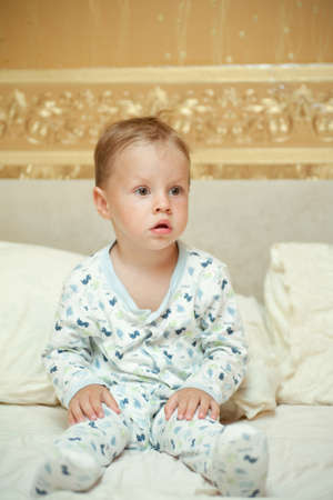 in a bed the woken-up boy in a pajamas sits photo