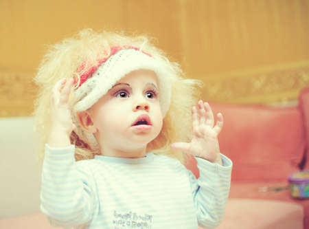 nurser: the kid in a wig and with cosmetics on a face Stock Photo