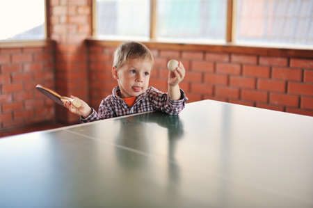 the child with a racket and a ball plays table tennis
