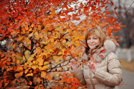 the woman in a white coat poses in the autumn wood photo