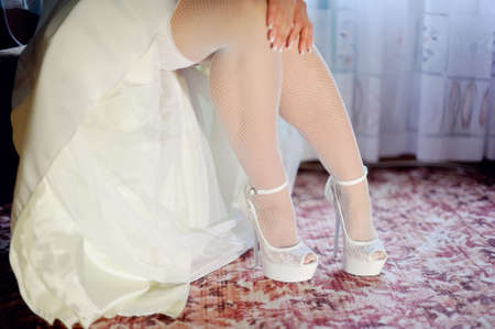 beautiful legs of the bride in white stockings and shoes photo