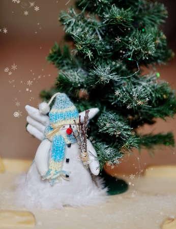 toy angel a snowman in a blue cap under a fir-tree photo