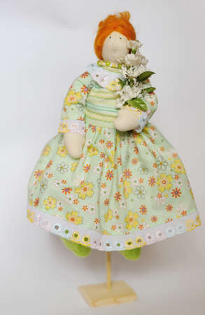 handwork doll in a dress and red hair with flowers photo