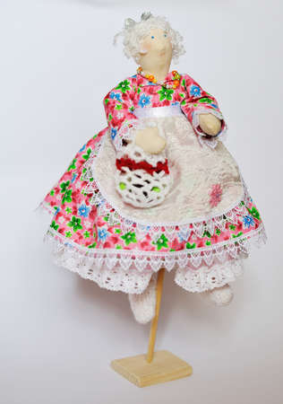 handwork doll in a dress with white hair and a basket in hands photo