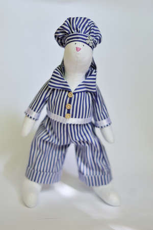 the doll a tilde hare in a striped suit sits photo
