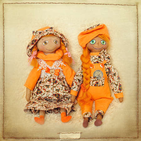 two dolls of handwork in orange suits photo