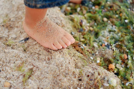 on the sea coast in algas there is a children s foot in sand photo