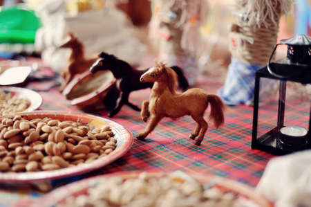 on a table there are plates with different nuts and toy horses photo