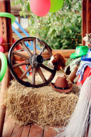 western attire: on a haystack the brown cowboy s hat and a wooden wheel lies Stock Photo