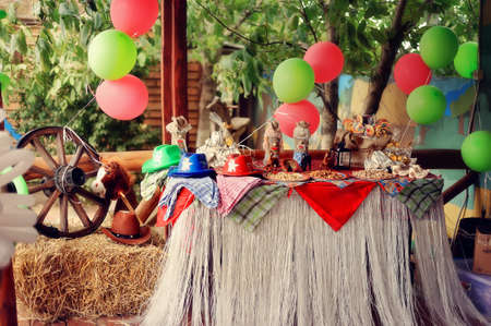 scenery of a cowboy s holiday - multi-colored balloons, hats, scarfs and a wooden wheel photo