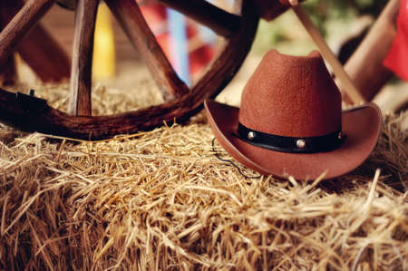 on a haystack the brown cowboy s hat and a wooden wheel lies Stock Photo