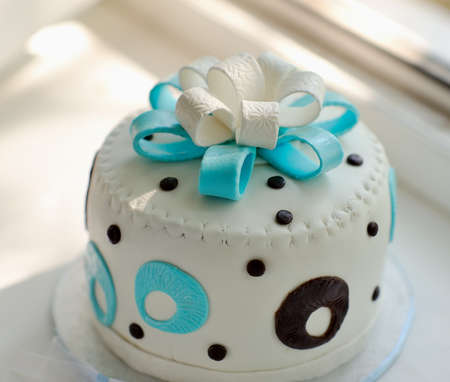the white cream pie is decorated with a blue bow and drawing photo