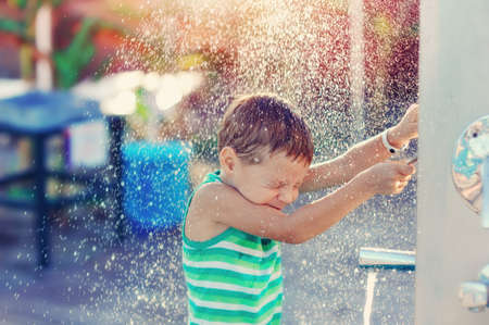 boy having fun with pool fountain shot during summer time Stock fotó