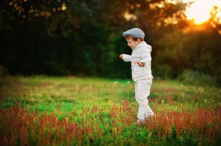 unity small flower: boy in a white suit walking in a meadow with wild flowers