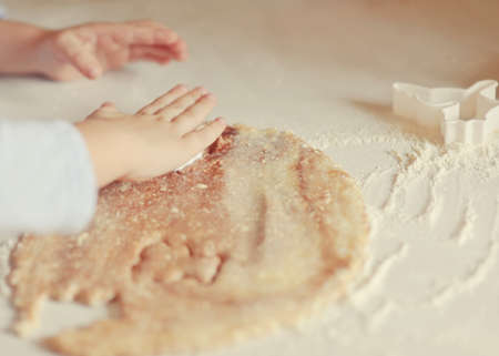Children s hands make molds for pastry dough photo