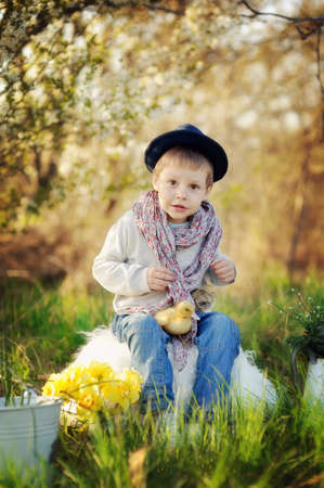 boy sitting outdoors in a hat with ducks and chickens photo